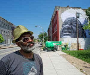 Jetsonorama in front of his mural at Barclay Street and Bowen Alley